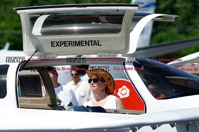 Kevin Bartram | Staff Marcia Janusz examines a Rutan Defiant airplane at the second annual Wings and Wheels show at Robertson Airport in Plainville on Sunday. The event featured hundreds of cars along with aircraft, games and entertainment.