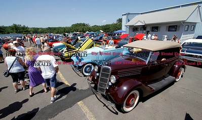 Kevin Bartram | Staff Visitors stroll past classic cars at the second annual Wings and Wheels show at Robertson Airport in Plainville on Sunday. The event featured hundreds of cars along with aircraft, games and entertainment.