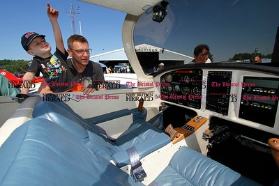 Kevin Bartram | Staff Gavin Malec, 3, and his father Eric Malec check out a Rutan Defiant at the second annual Wings and Wheels show at Robertson Airport in Plainville on Sunday. The event featured hundreds of cars along with aircraft, games and entertainment.