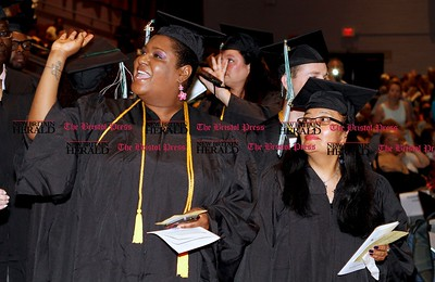 Kevin Bartram | Staff Tanarhn Smith-Dixon waves to friends and family as she walks into Charter Oak College graduation on Sunday at Welte Hall on the campus of Central Connecticut State University in New Britain. Charter Oak offers online degree programs and accelerated completion plans.