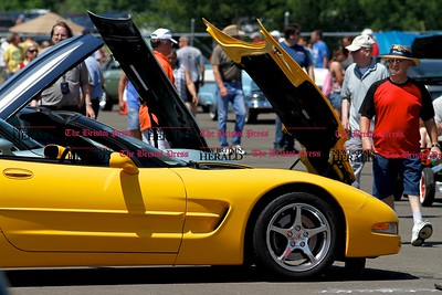 Kevin Bartram | Staff Spectators walk past rows of cars at the second annual Wings and Wheels show at Robertson Airport in Plainville on Sunday. The event featured hundreds of cars along with aircraft, games and entertainment.