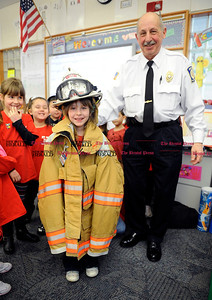 3/1/2013 Mike Orazzi | Staff Bristol Fire Marshal Denis Peri with Lilah Aakjar wears some fire fighting equipment at the Mt. View School on Friday.