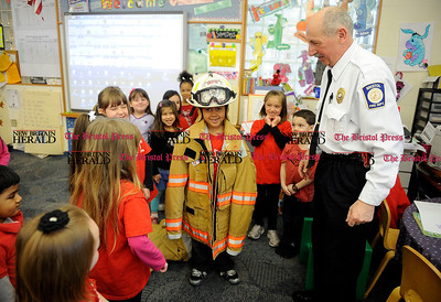 3/1/2013 Mike Orazzi | Staff Bristol Fire Marshal Denis Peri as Charles Cherry wears some fire fighting equipment at the Mt. View School on Friday.