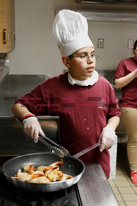 Kevin Bartram | Staff Angel Cruz, 12, sautées shrimp during a culinary class at the New Britain Boys and Girls Club on Wednesday. Kids at the club learned about healthy cooking during the weekly class.