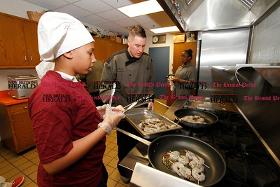 Kevin Bartram | Staff Chef Jeffrey Taddeo watches while Diamond Irving sautées shrimp during a culinary class at the New Britain Boys and Girls Club on Wednesday. Kids at the club learned about healthy cooking during the weekly class.