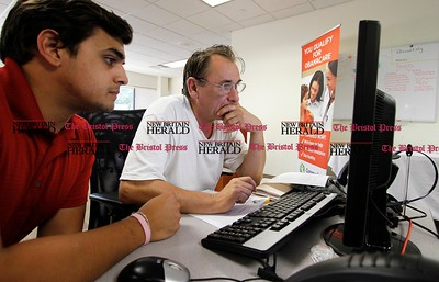 Kevin Bartram | Staff Bogie Dudek, right, is assisted by Sagar Parekh during an Affordable Care Act enrollment fair for patients at Community Health Center, Inc. in New Britain on Tuesday. Tuesday was the first day to apply for health insurance under the Affordable Care Act.