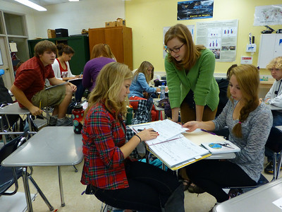 """Molly Carpenter (in green sweater) helping students understand the results of the """"unknown powders"""" lab"""