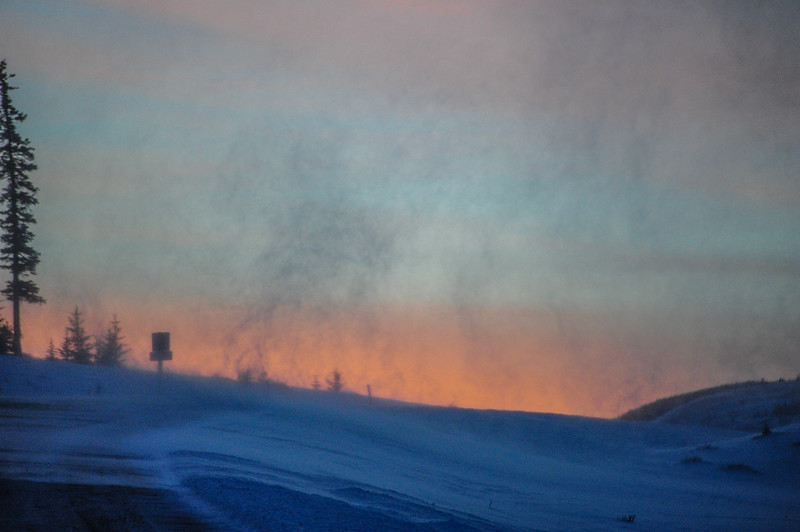early morning sunrise with blowing snow