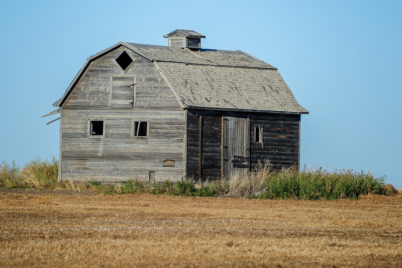 this lonely barn stood alone quite far from the highway