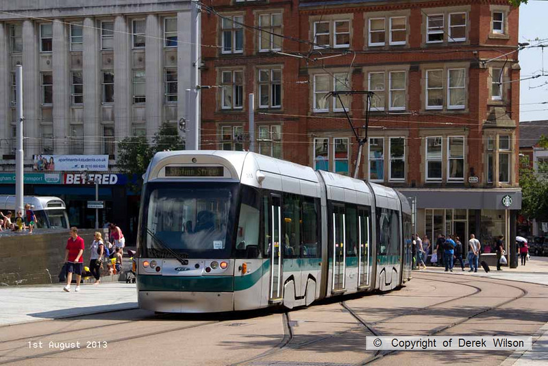 130801-025     Nottingham Express Transit (NET) Incentro class tram no 215 Brian Clough passes the old market square, on it's way to the Station Street terminus.