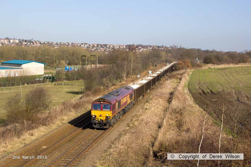 130302-005     DB Schenker class 66/0 no. 66077 is captured from the A617 Sutton bypass, powering train 6Z16, 1015 Cottam Power Station to Portbury Coal Terminal  conveying gypsum in open box wagons.