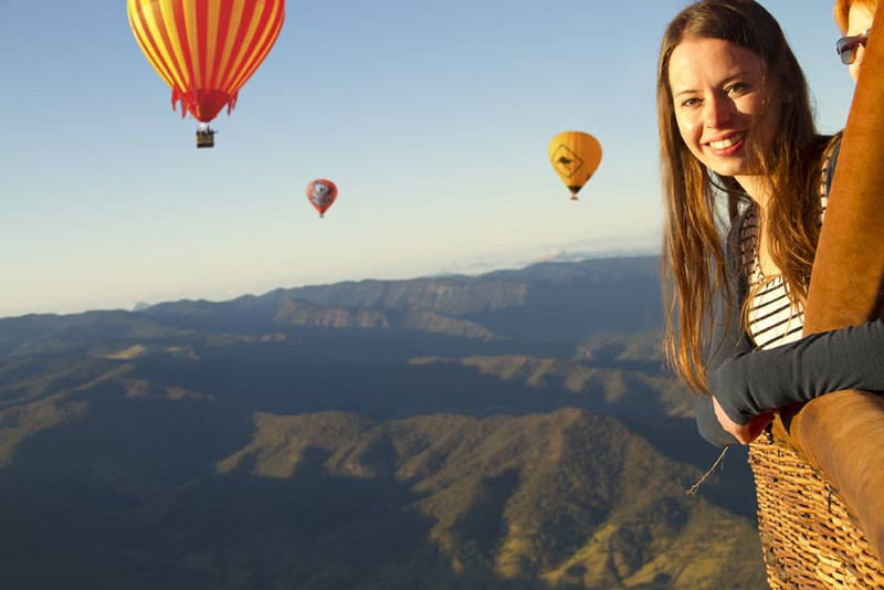 Hot-Air-Balloon-Gold-Coast-Brisbane-Young-woman-smiling-leaning-out-with-balloons-behind_sml