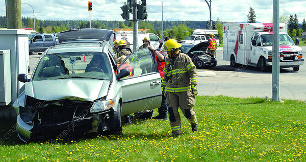 BC Ambulance paramedics and Prince George firefighters help the driver of a van that was involved in a collision with a car at highway 16 west and Ferry Avenue Wednesday afternoon. traffic on highway 16 westbound was down to one lane while crews dealt with the accident. citizen photo by Brent Braaten    May 15 2013