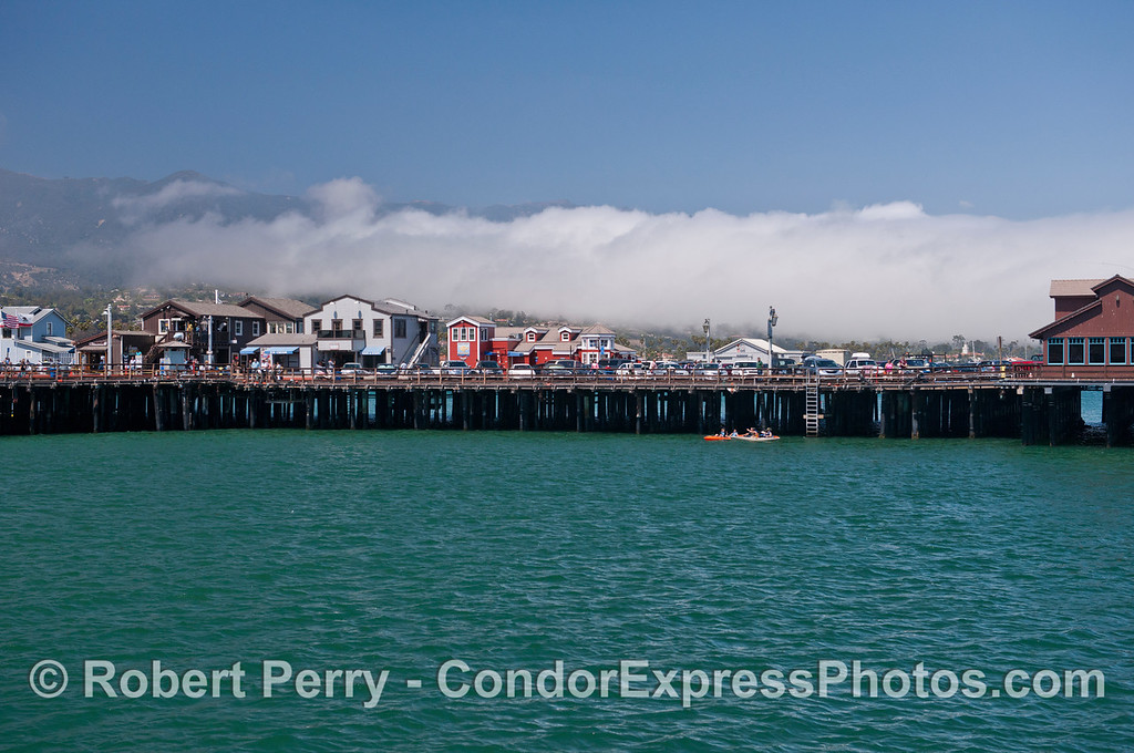 Sterns Wharf in Santa Barbara is seen with a fog bank moving up the mountain slopes in the background.