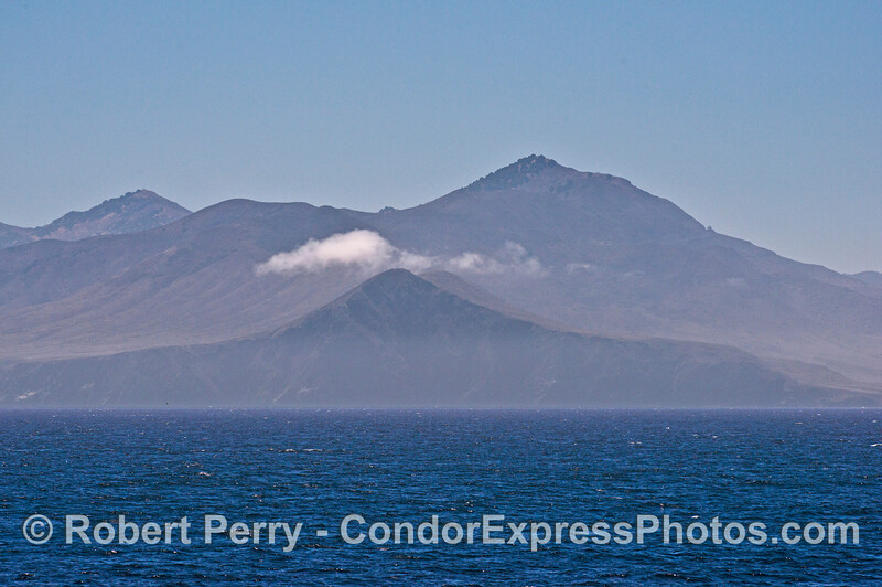 The West End of Santa Cruz Island is seen looking east with a cap of clouds caused by the wind.