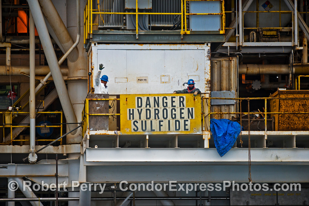 Workers on Platform Holly pose for a moment with the Hydrogen sulfide warning sign.