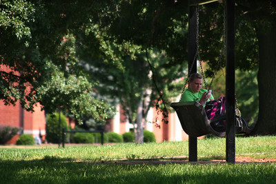A Gardner-Webb student enjoys some music as she takes a break on a swing.
