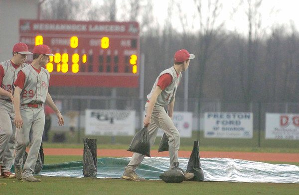 Erica Galvin/NEWS<br /> Neshannock team members hurry to cover the dirt pitching mound as rain moved into the area in the fifth inning.