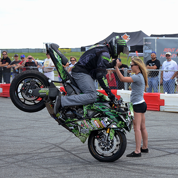 "Eric Hoenshell of ""Team No Limit"" give volunteer Leila Wulderk a ""High Five"" as he brings his stunt cycle to a stand up stop inches away from her during the motorcycle stunt show at the AHRMA races on Sunday, August 4.<br /> <br /> ©Sam Feinstein"