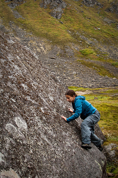 Amy steps delicately into a long and featureless slab, with slimy moss and lichen threatening to deny her access to the topout.