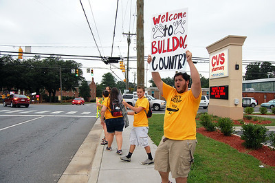 Students cheer at the stoplight to greet incoming Freshmen as they arrive on the campus for orientation.