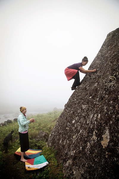 Fog dims the surrounding scenery as Sandra nears the topout of a boulder problem.