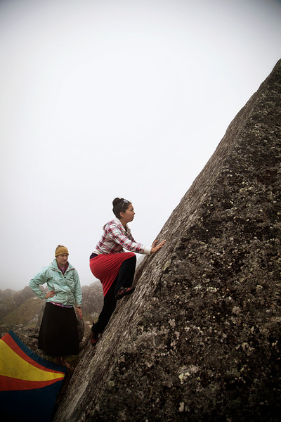 Sandra moves up on a steep slab with the fog drifting thick all around.