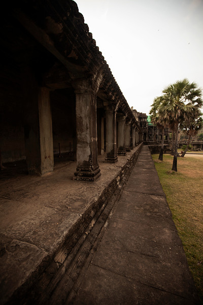 The long-standing stone walls and towers of Angkor Wat loom impressively all around.