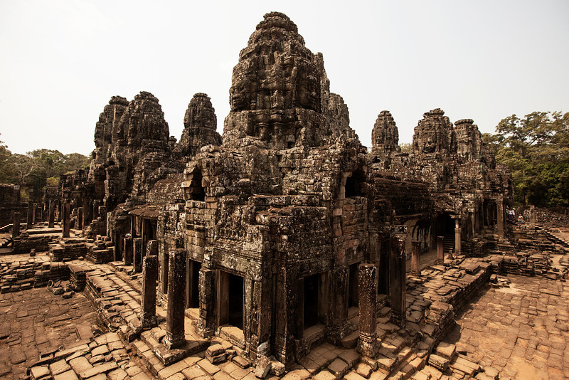 Bayon features a crumbling pyramid temple with intriguing faces on its towers, enduring the tests of time as they look out across the Cambodian landscape.