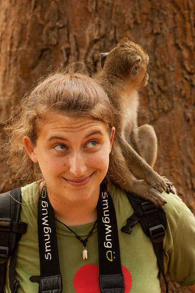 A monkey perches atop Tracy's shoulder near the ruins of Angkor Thom.