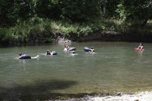 Elijah and other campers swimming.  I think he's one of the two heads not in a tube.