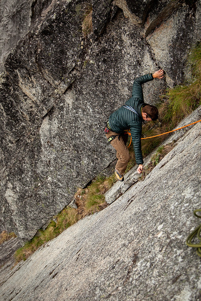 Matt moves through some grassy terrain, finishing up the first pitch of <i>Rise 5.9</i>.