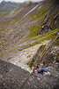 A slightly awkward topout leaves Tracy searching for handholds at the belay atop pitch four.