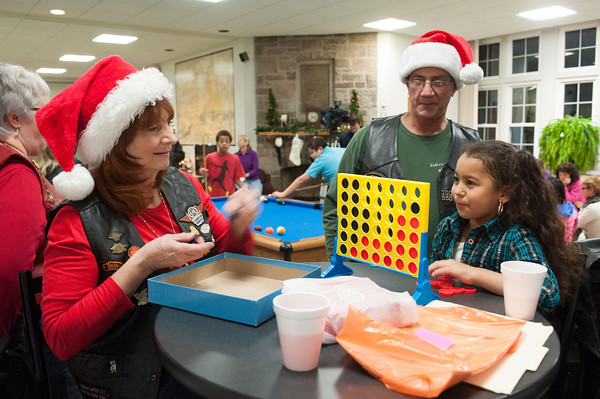 131202 Harley Christmas JOED VIERA/STAFF PHOTOGRAPHER Lockport, NY- <br /> Harley Owners Group member Paul Isham watches fellow member Jude Wildhagen play a game of Connect Four with Wydham Lawn student Julissa Vasquez (8) at the school on Monday Dec 2nd, 2013.