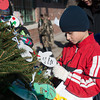 131203 Christmas Drive JOED VIERA/STAFF PHOTOGRAPHER Gasport, NY-Roylton Hartland fourth grader Collin Martin(9) places a mitten on a the Christmas tree outside of the Gasport post office on Tuesday Dec 3rd, 2013. The mittens have gift recommendations written on them for needy children.