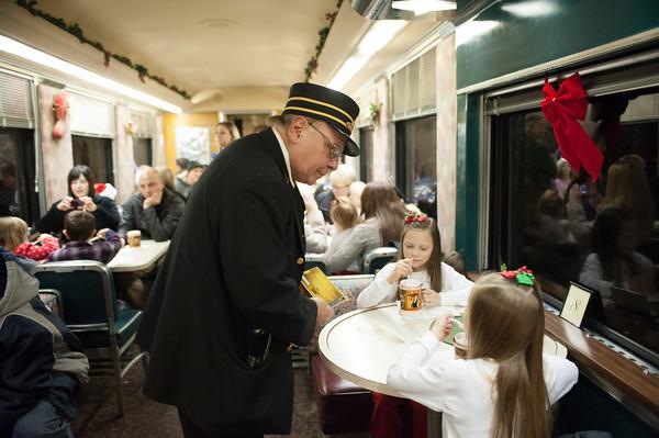 131208 Polar Express JOED VIERA/STAFF PHOTOGRAPHER Medina, NY-The Polar Express conductor checks on a passengers ticket on Sunday Dec 8th, 2013.