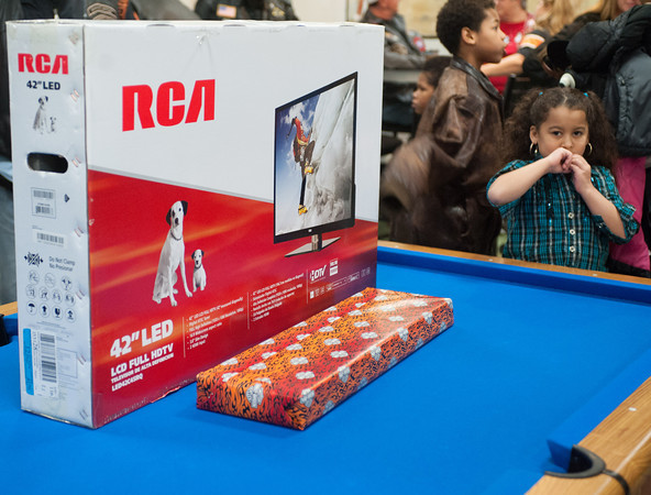 131202 Harley Christmas JOED VIERA/STAFF PHOTOGRAPHER Lockport, NY- Julissa Vasquez stands next to a 42 inch television. The Television was this years gift from the Niagara Falls Harley Owners Group to Wyndham Lawn on Monday Dec 2nd, 2013.