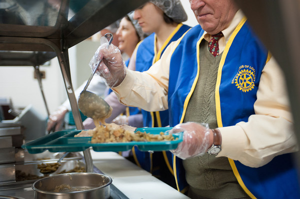 131209 Rotary soup JOED VIERA/STAFF PHOTOGRAPHER Lockport, NY-Rotary club volunteer Eugene Urban puts gravy on turkey at the Salvation Army during the clubs annual turkey dinner on Monday Dec 9th, 2013.