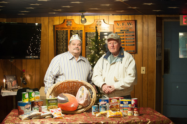 131205 VFW Food Drive JOED VIERA/STAFF PHOTOGRAPHER Lockport, NY-Senior Vice Director of Lockports VFW post 2535 Raymond Pierce and Korean War Veteran Robert Macdonald stand behind food donations intended to feed 10 families for Christmas. Those interested in making a donation can can call Mr. Pierce at (716) 471-3507, bring non perishable food items to the Post, send cash, or make checks payable to LOCV and mail to The Veterans of Foreign Wars at 112 Caledonia Street, Lockport, NY 14094  Thursday Dec 5th, 2013.