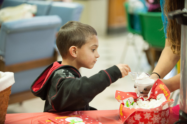 """131130 YMCA Crafts JOED VIERA/STAFF PHOTOGRAPHER Lockport, NY- Mason Owens puts some marshmallows in his hot chocolate at the YMCA on Saturday Nov 30th, 2013. The YMCA hosted arts and  crafts and distibuted glowing bracelets for this years Christmas on the canal """"Parade in the Dark""""."""