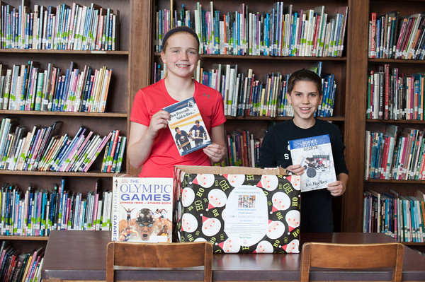 131205 Newfane Book Drive JOED VIERA/STAFF PHOTOGRAPHER Newfane, NY-Newfane Middle School students Alexa Littman and Tyler Gmerek sit with a donation box for books benefiting a Sandy Hook  charity started by the students and school on Thursday Dec 5th, 2013.
