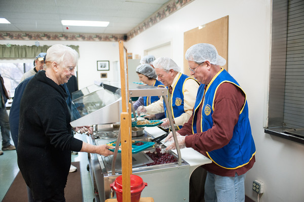 131209 Rotary soup JOED VIERA/STAFF PHOTOGRAPHER Lockport, NY-Rotary club volunteer Michael Alexander serves Ada Eberheart during the club's annual turkey dinner at the Salvation Army on Monday Dec 9th, 2013.