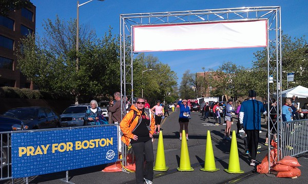 In light of the Boston Marathon bombings the week before, security and awareness were heightened for this race.  These fences established a secure perimeter around the finish line, while Coach Jenny (in pink, who finished 6th overall and 1st in her age group) waits for her slower athletes.