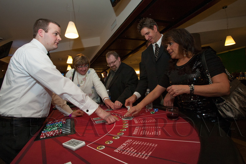 "Jason Milam deals at the poker table for Kent Krebs and Pauline Vigil at the poker table.  ""Mile High Dreams Gala,"" benefiting Kroenke Sports Charities, at the Pepsi Center in Denver, Colorado, on Monday, Jan. 21, 2013.<br /> Photo Steve Peterson"