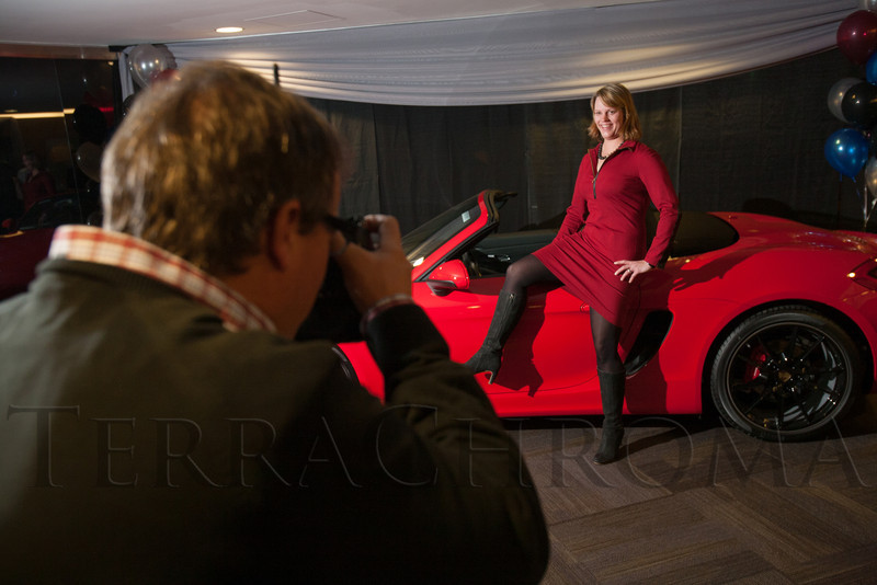 "Garrett Ellwood shoots a photo of Christine Pflueger with a Porsche.  ""Mile High Dreams Gala,"" benefiting Kroenke Sports Charities, at the Pepsi Center in Denver, Colorado, on Monday, Jan. 21, 2013.<br /> Photo Steve Peterson"