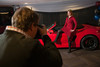 """Garrett Ellwood shoots a photo of Christine Pflueger with a Porsche.  """"Mile High Dreams Gala,"""" benefiting Kroenke Sports Charities, at the Pepsi Center in Denver, Colorado, on Monday, Jan. 21, 2013.<br /> Photo Steve Peterson"""