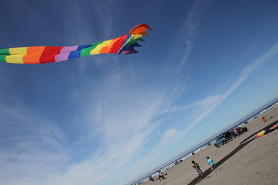 Kids hiding in the shadow of a rainbow kite