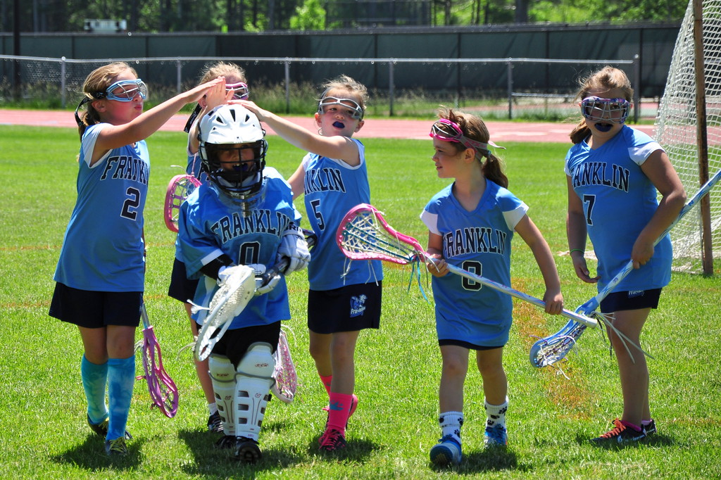 Anya being congratulated after playing goal for her lacrosse team