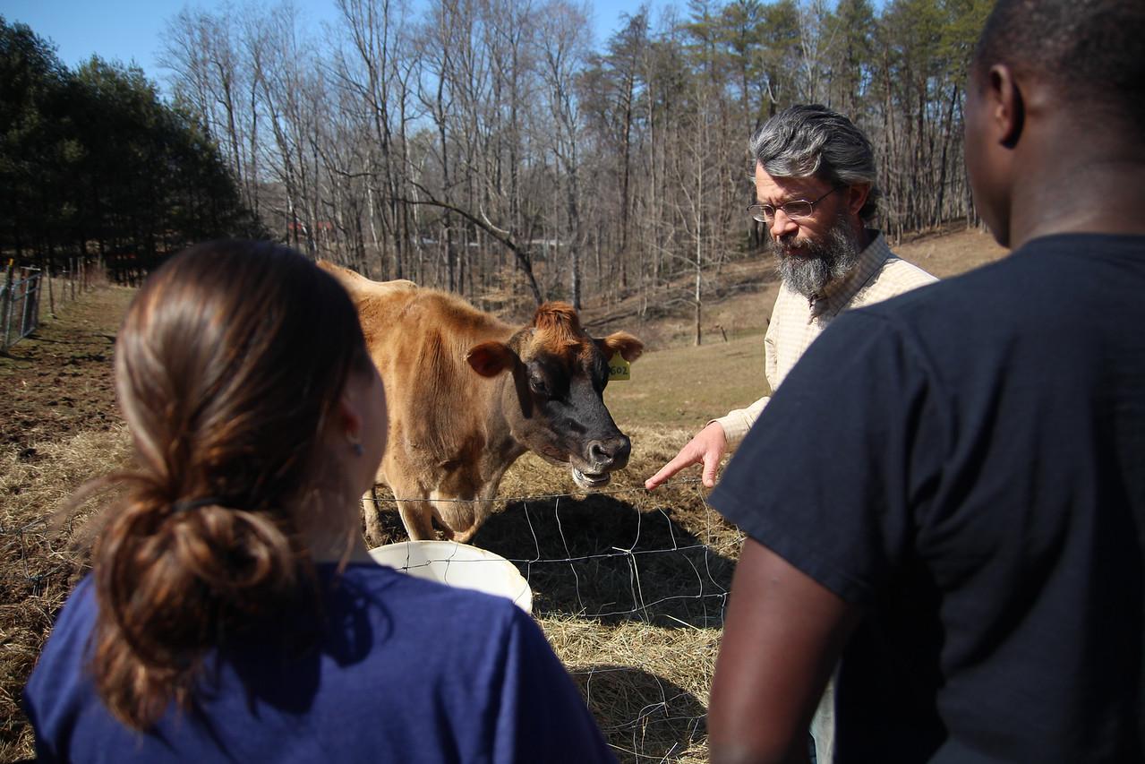John Hartman explains life on a farm to Sarah Covarrubias and Darelle Dove.