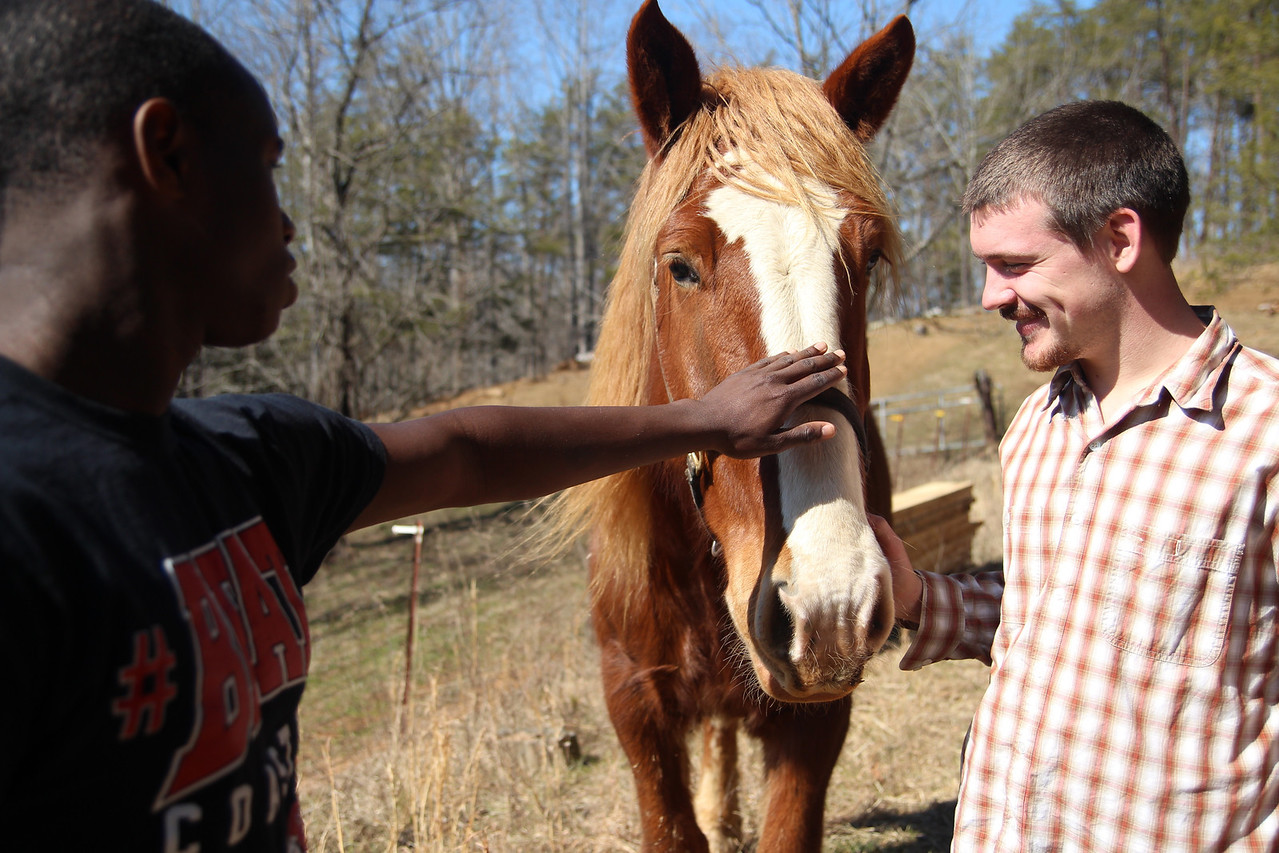 Darrelle Dove pets a horse for the first time while Devan Vandenbark holds it steady.